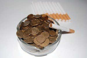 an ashtray filled with pennies and a cigarette