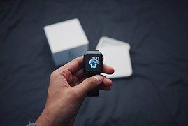 A photo of a person using a mobile phone and bluetooth watch