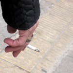 A stock photo of a hand holding a cigarette outside on the street in NYC